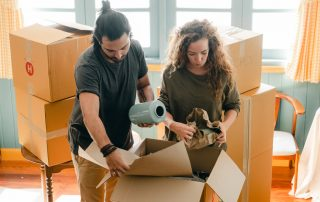 couple packing belongings into moving boxes