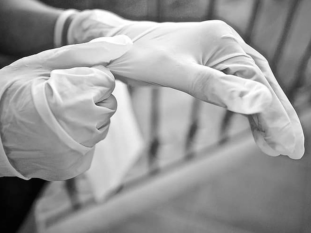Two hands putting on white gloves